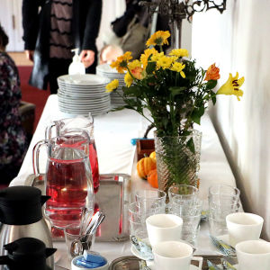 Ett bord dukat med en vas med blommor, två saftkannor och kaffekoppar.