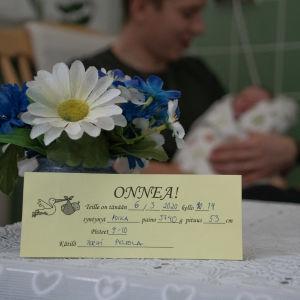 """En gul lapp med texten """"onnea"""" på och information om den nyfödda. Pappan och sonen syns i bakgrunden då de sitter i gungstolen."""