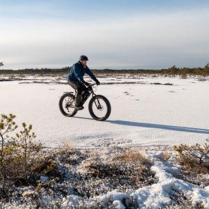 En terrängcyklist som cyklar på skaren vintertid.