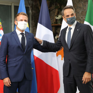 Emmanuel Macron ja Kyriakos Mitsotakis poseeraavat kuvaajille toisiaan käsivarsista pidellen