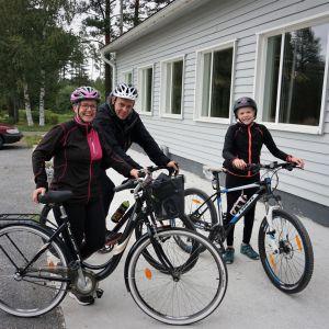 En familj på cykel står framför en vit byggnad.
