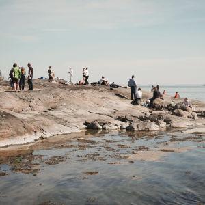 Lukiolaisia ja muita ihmisiä rantakalliolla Dalskär-saarella.