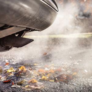 auto ja pakokaasua syksyisessä maisemassa