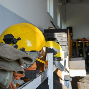 En gul brandmanshjälm och handskar på en låg hylla. I bakgrunden syns knaggar var det hänger brandmanskläder.