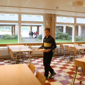 pojke bär bricka i skolmatsal