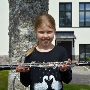 En flicka håller vågrätt en oboe i sina händer.