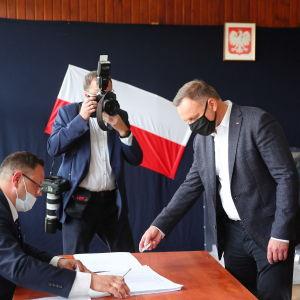 President Andrzej Duda röstar i presidentvalet i Polen den 12 juli 2020. En man ger en valsedel till en annan man, båda bär munskydd. En tredje man fotograferar.