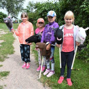 Fyra flickor med käpphästar i händerna.