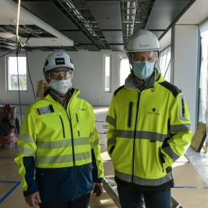 Två män i arbetskläder, hjälm, skyddsglasögon och munskydd står i ett stort rum som är under konstruktion.
