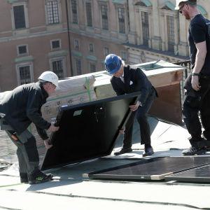 Kung Carl XVI Gustaf hjälper att installera en solpanel på Stockholms slotts tak.
