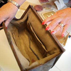 Man ser ner in en handväska som två händer öppnar. Det är rött nagellack på naglarna.