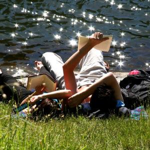 Personer ligger i gräset och njuter av solskenet.