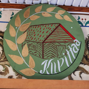 """Rund grönmålad skylt med bild på en stuga och gyllene blad samt texten """"Kupittaa"""" i vitt."""