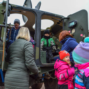 Dagisbarn inne i ett militärfordon.