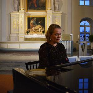 Mörkklädd kvinna sitter vid piano.
