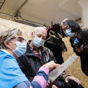 Rita Solla sekä Pertti Solla tutustuvat koronavirusrokotuksen jälkeisiin ohjeisiin Carola Möllerin johdolla 1. helmikuuta.