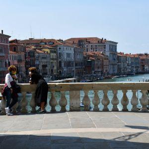 Två kvinnor med munskydd står lutade mot varandra och mot ett broräcke i vit sten. Bakom räcket syns en kanal i Venedig och husen på bägge sidor.