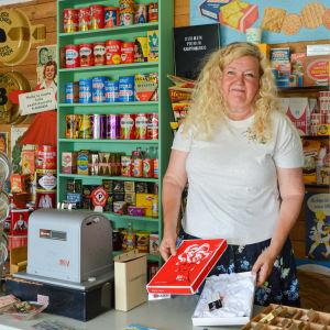 Minna Järvinen står bakom kassan i en butiksmiljö från 50- och 60-talet.