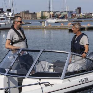 Markkinointijohtaja Tuomas Kataila ja operatiivinen johtaja Akseli Sajaniemi yritksen vuokraveneessä Lauttasaaren rannassa