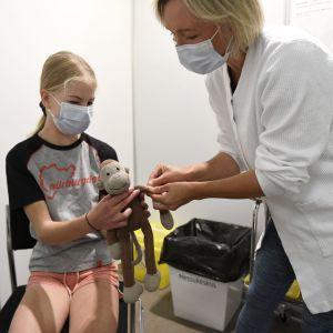 Helsinkiläinen Tilda Pitkänen, 12 vuotta, sai ensimmäisen koronavirusrokotteensa ja Tildan lemmikkiapina Apa sai käsivarteensa laastarin sairaanhoitaja Inka Ruosteenojalta Messukeskuksen koronarokotuspisteellä Helsingissä maanantaina 9. elokuuta 2021.