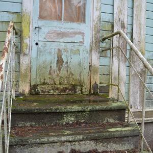Dörren och trappan på baksidan av Villa Kolkka på Runsala är vattenskadad och mögelskadad.