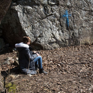 en flicka sitter på en sten