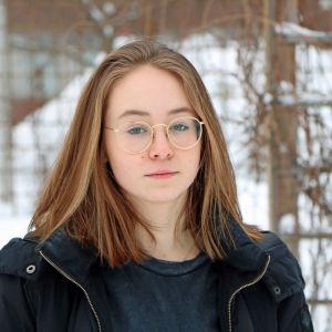 En ung kvinna med långt brunt hår och runda glasögon står utomhus med vinterlandskap i bakgrunden.