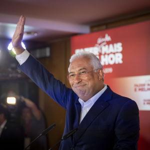 Premiärministern och partiledaren Antonio Costa gör en triumferande gest från sin talarstol vid valvakan i Lissabon.