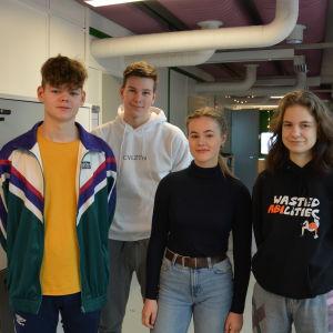Fyra ungdomar står på rad i en skolkorridor.