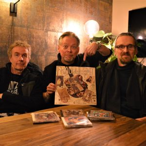 Tre män som håller i en LP-skiva. På bordet framför sig har de fyra cd-skivor.