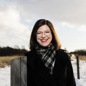 Anni Sinnemäki ler mot kameran i ett vinterlandskap