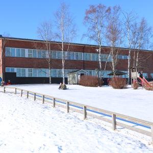 En röd tegelbyggnad. Framför byggnaden åker barn ner för en pulkabacke.