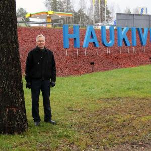 Haukivuoren aluejohtokunnan puheenjohtaja Leo Laukkanen Haukivuori-kyltin edustalla.