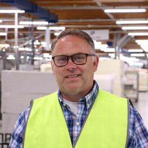 En man med kort grått hår och glasögon står i en fabrik.