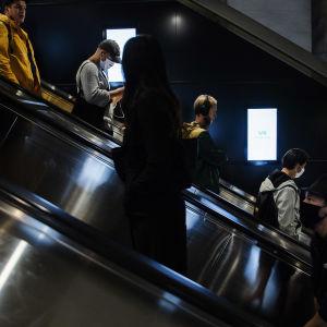 Kuvassa on ihmisiä metroasemalla Helsingin keskustassa elokuussa 2020.
