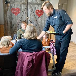 Joni Sarajärvi työssään tarjoilemassa asiakkaille Lapland Hotels Luostotunturin ravintolassa.