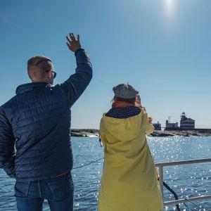 Mies ja nainen moottoriveneen kannella selin kameraan: mies heilauttaa kättään. Taustalla majakkasaari.
