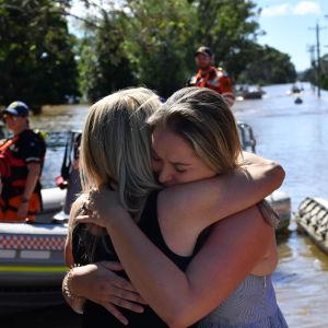 En mamma och dotter kramas då de återförenats efter att ha evakuerat undan översvämningar i Australien