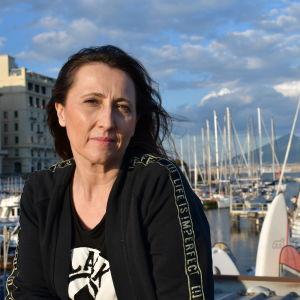 En kvinna vid en blåsig hamn.