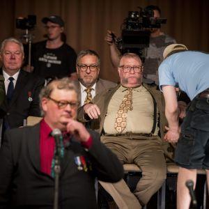 Näyttelijä Kari Väänänen (takki auki keskellä) Homeliuksen roolissa Fingerpori-elokuvan kuvauksissa Turussa 24. toukokuuta 2018. Elokuvan tarina pohjautuu sarjakuvataiteilija Pertti Jarlan luomaan Fingerpori-sarjakuvaan ja sen hahmoihin.