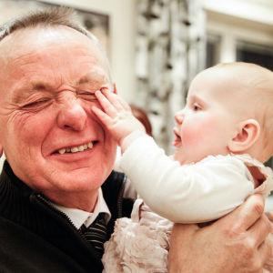 Äldre man leker med en baby.