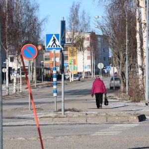 En kvinna med rosa jacka går på en gata i Närpes centrum.