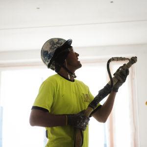 Två hjälmförsedda byggarbetare i gula t-skjortor inne i ett hus på ett bygge.