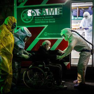 Ambulanspersonal flyttade äldre coronasmittade patienter från ett mentalsjukhus till andra sjukhus i Buenos Aires på söndag kväll.