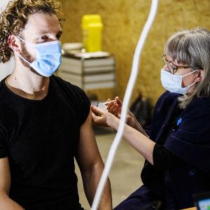 En man vaccineras med coronavaccinet i Helsingfors i januari 2021. En kvinnlig sjukskötare ger vaccinet.