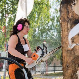 Kvinna i svart topp och pinka hörselskydd sågar en stor stock med motorsåg.