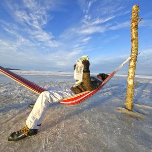 Man läser en tidning liggande i en hängmatta på isen.