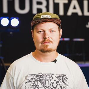 Ossi Valpio katsoo suoraan kameraan. Hänellä on lippis päässään.