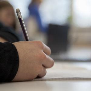 hand som skriver med penna.