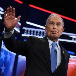 En gråhårig man i kostym håller upp ena handen i hälsning.